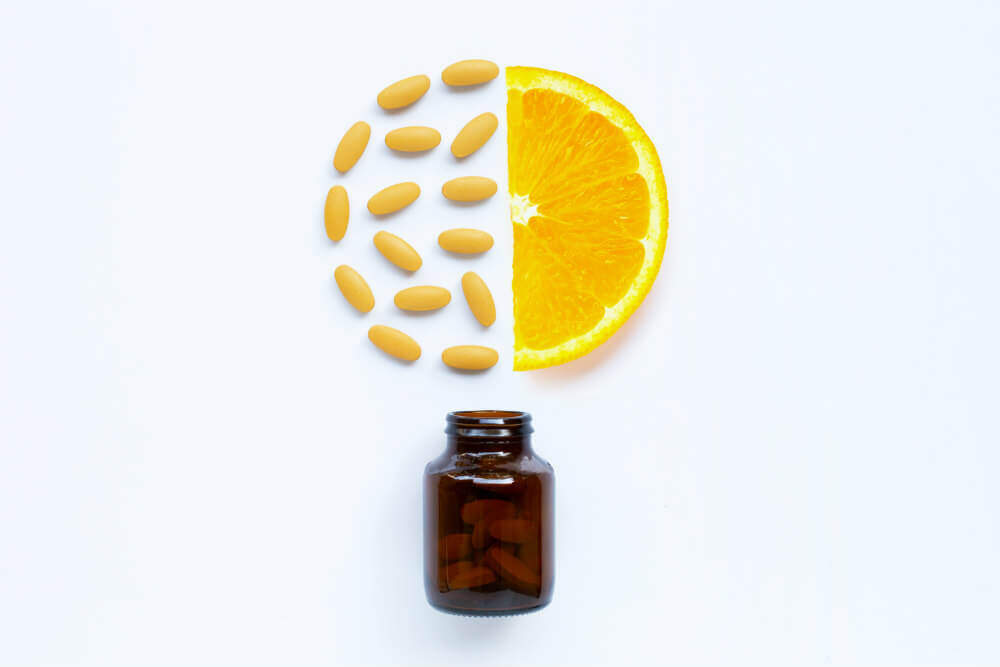 Vitamin C bottle and pills with orange fruit on white